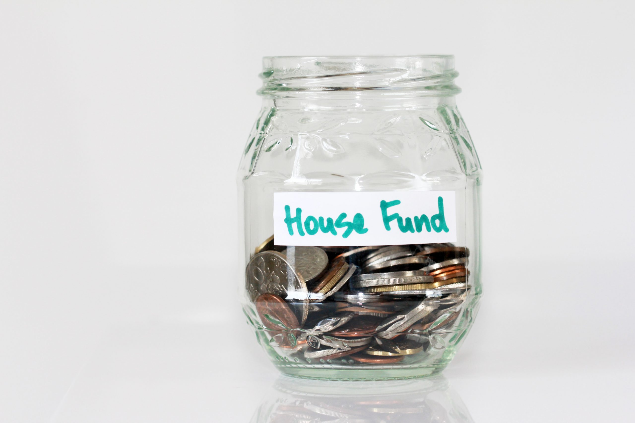 Picture of savings jar filled with money and labelled house fund